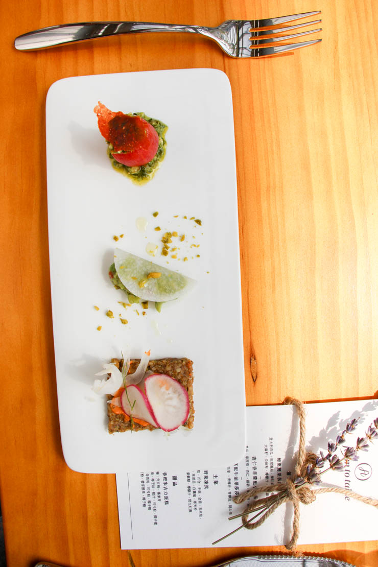 raw vegan appetizers: skinless tomato with pesto, pocketed guacamole, and flaxseed cracker with smoked cashew cream
